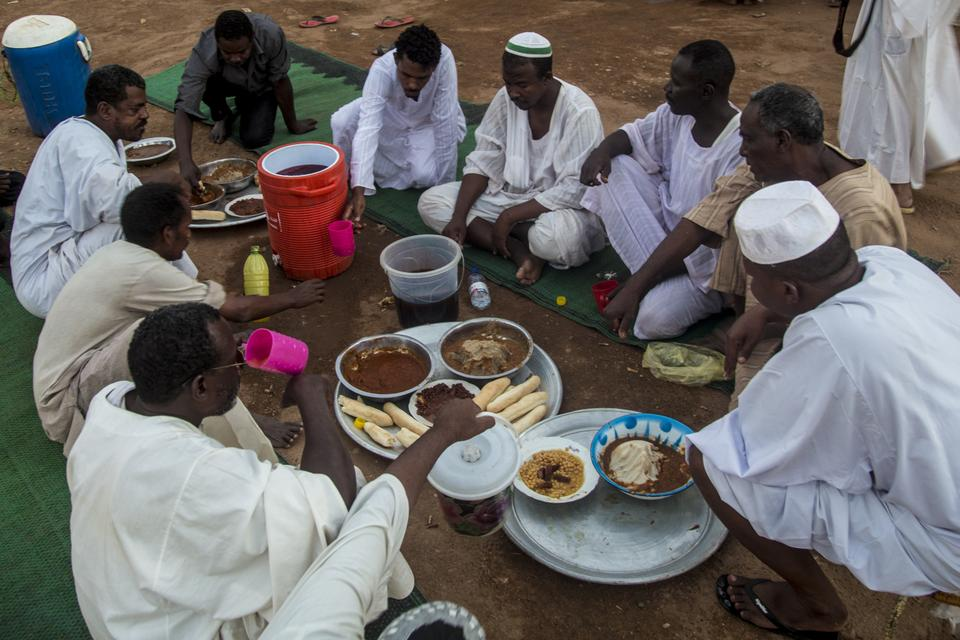 Sudanese people break their fast during the first iftar dinner of Ramadan in Khartoum, Sudan on April 25, 2020.