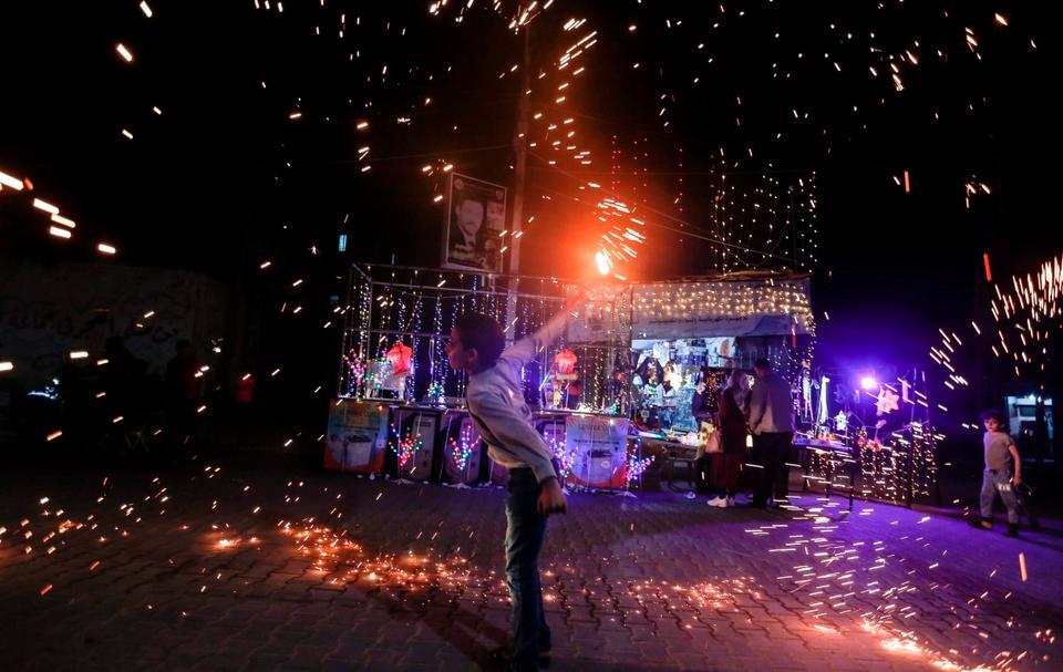 A Palestinian boy waves a homemade sparkler firework as he celebrates ahead of the holy fasting month, amid concerns about the spread of the coronavirus disease (COVID-19), in the southern Gaza Strip.