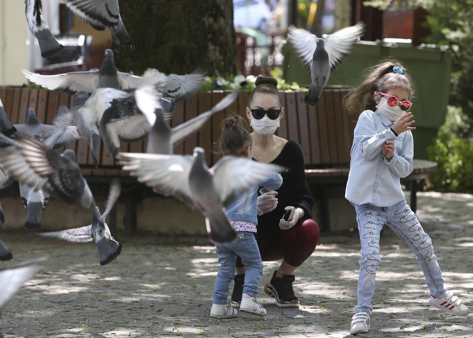 A child feeds pigeons at Tunali Hilmi Street in Ankara, Turkey on May 13, 2020.