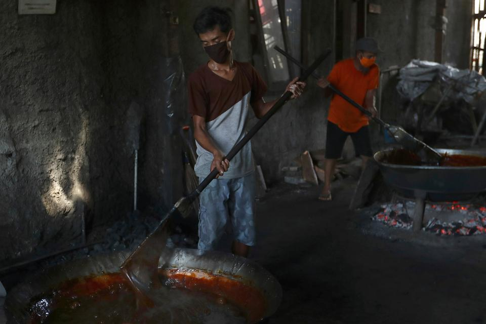 Workers wearing face masks make a toffee-like traditional sweet cake called
