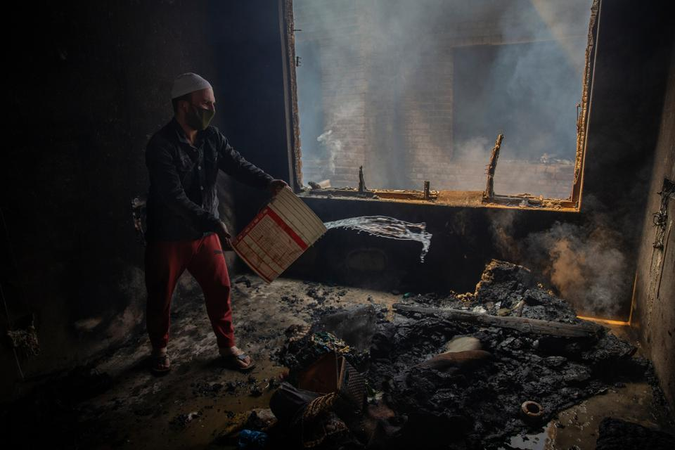 A Kashmiri man douses a fire in a house that was allegedly damaged by Indian armed forces during a gun-battle in Srinagar on May 19 in Indian controlled Kashmir.