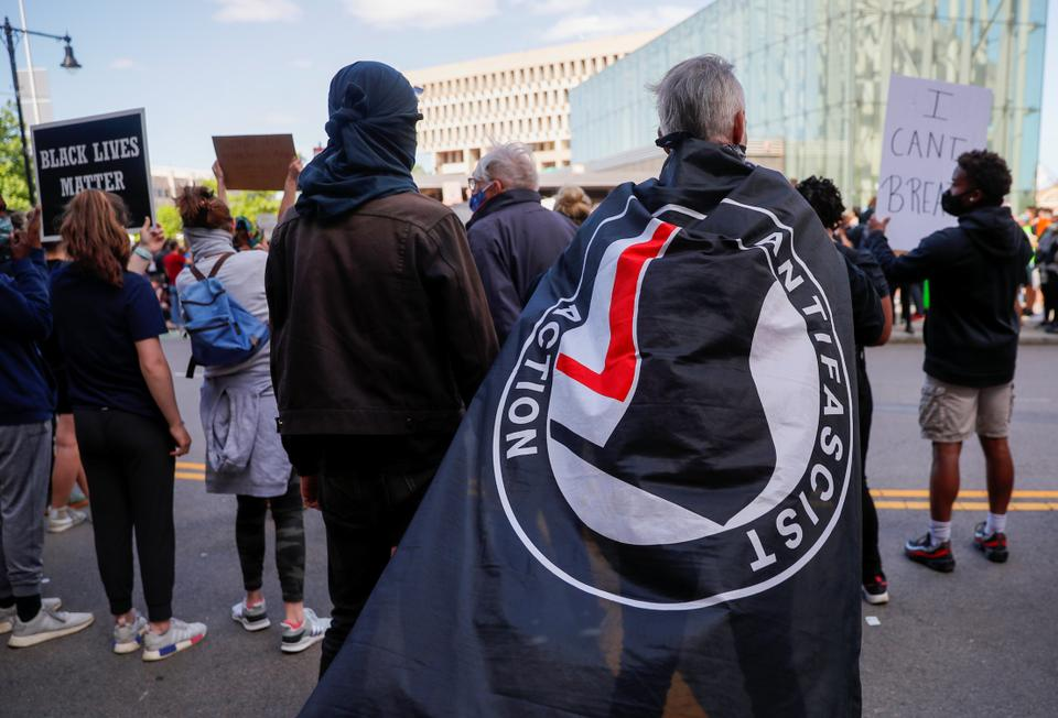 A protester carries an Antifascist Action flag at a rally following the death of George Floyd in Minneapolis police custody, in Boston, Massachusetts, US, May 31, 2020.