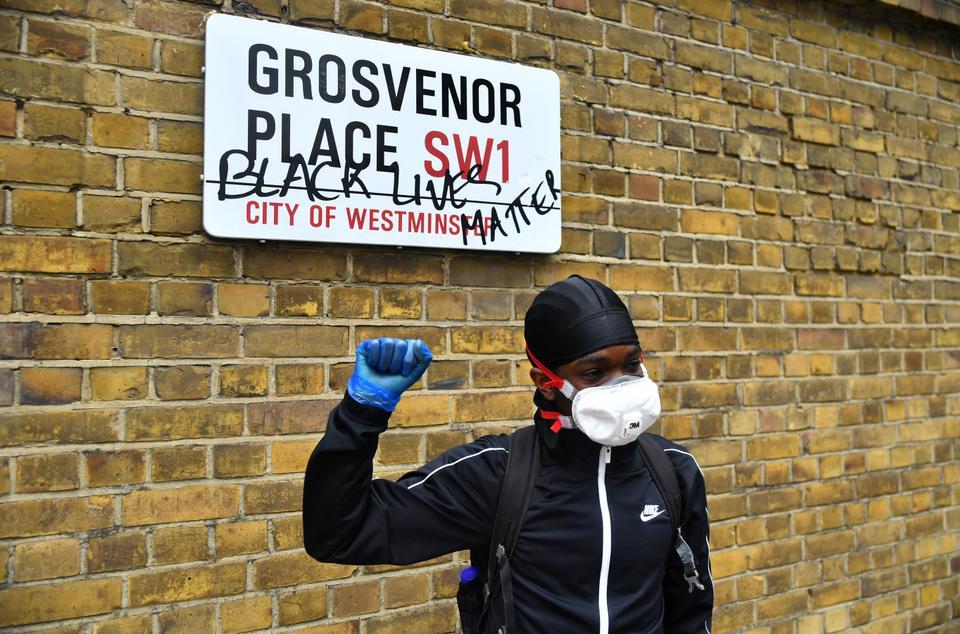 Yüz maskesi giyen bir adam bir Grosvenor Place yol işaret yanında bir mesajla tepki verir.