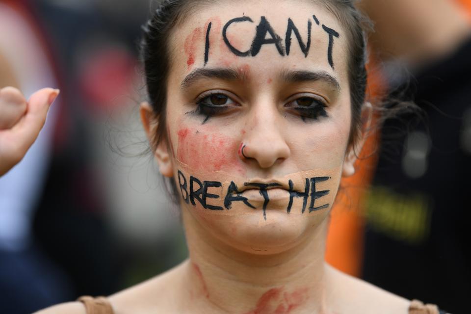 Yüzünde boyalı bir mesaj olan bir kadın,