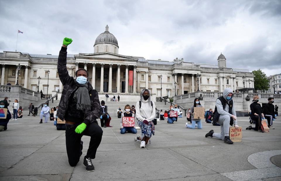 Minneapolis'te polis nezaretinde ölen George Floyd'un ölümünden sonra, Londra'daki Trafalgar Meydanı'ndaki Black Lives Matter protestosu sırasında maske takan ve işaret tutan insanlar diz çöküyor. Londra, İngiltere, 5 Haziran 2020.
