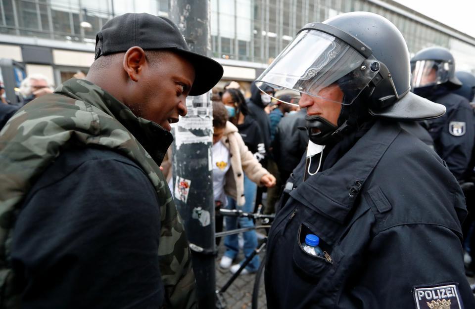 Bir gösterici, 6 Haziran 2020'de Berlin, Almanya'daki George Floyd'un Minneapolis polis gözetiminde ölümün ardından polis vahşeti ve ırksal eşitsizliğe karşı protesto sırasında bir polis memuruyla konuşur.