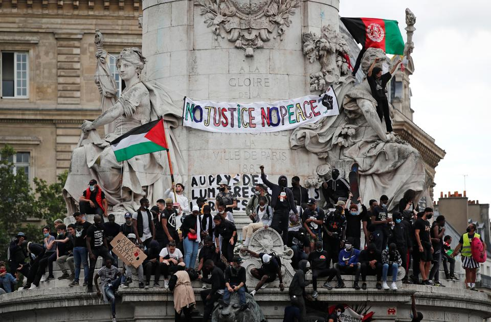 Demontrators stand on the Monument a la Republique during a protest against police brutality and the death in Minneapolis police custody of George Floyd, at the Place de la Republique square in Paris, France on June 13, 2020.