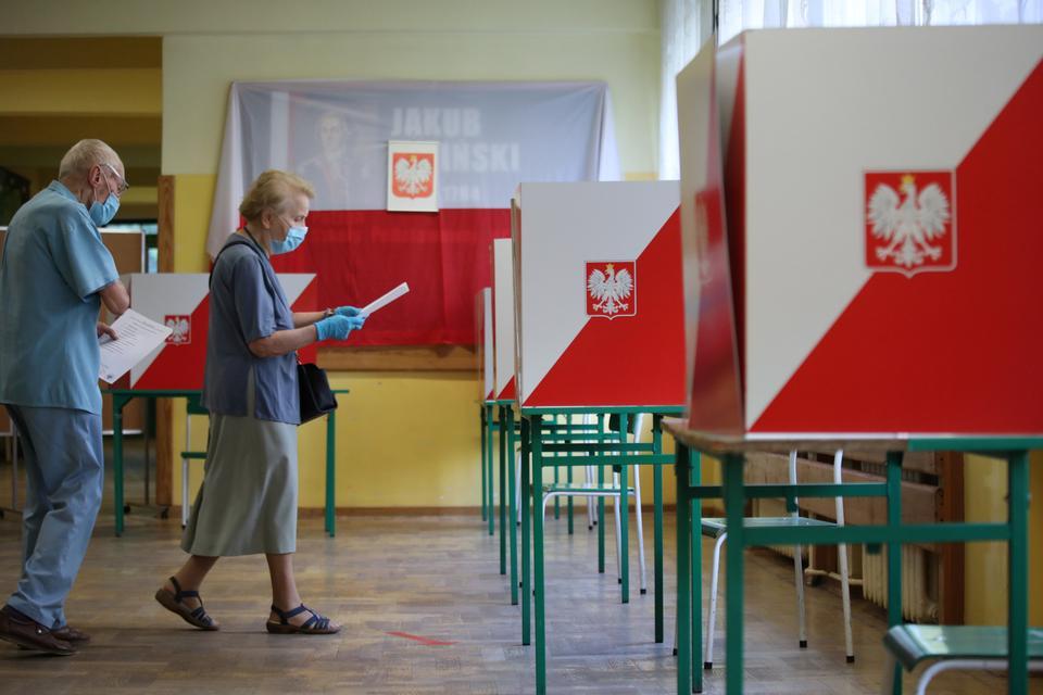 Koruyucu yüz maskeleri takan insanlar, 28 Haziran 2020'de Varşova, Polonya'daki bir seçim istasyonunda yapılan cumhurbaşkanlığı seçimlerinde oylamaya katılıyorlar.