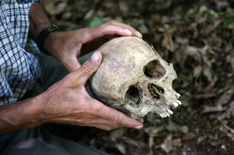 Srebrenica genocide survivor Ramiz Nukic looks at a skull that he found in the forest near Konjevic Polje, Bosnia and Herzegovina July 6, 2020. Nukic has made himself a promise, he will search for the remains of the people who went missing until the last of them is found.