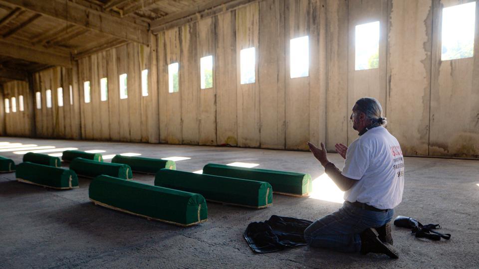 Bir adam 10 Temmuz 2020 Cuma günü Srebrenica, Bosna yakınlarındaki Potocari'deki eski BM üssündeki kurbanların tabutlarıyla dua ediyor.