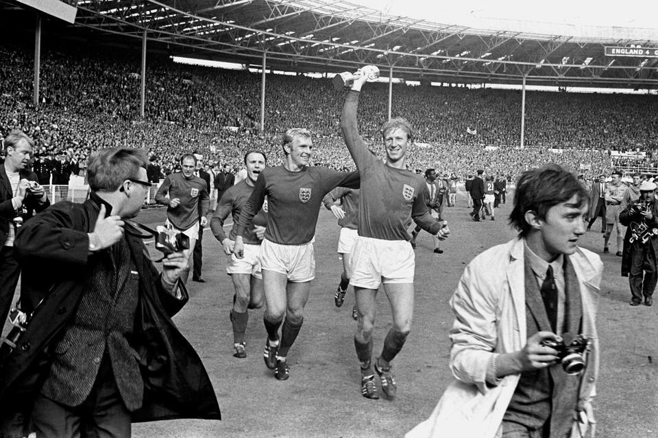 Fotoğraf: İngiltere'nin Jack Charlton, 30 Temmuz 1966'da Batı Almanya'da 4-2 galibiyetini takiben takım arkadaşı Bobby Moore ile Wembley etrafında geçit töreni yaparken Jules Rimet kupasını havada tutar.