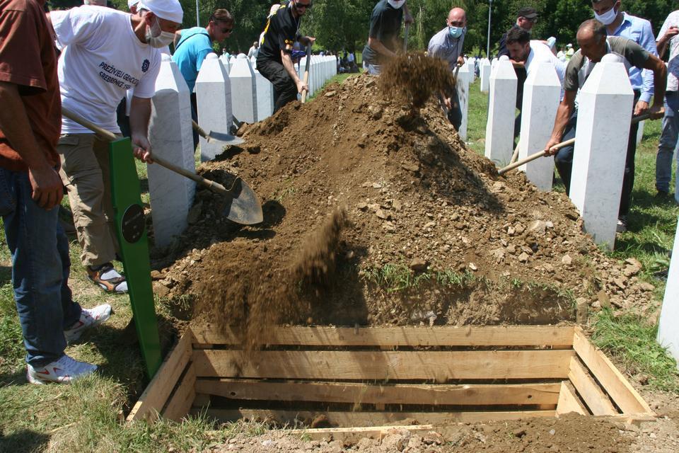 Bir grup adam, 11 Temmuz 2020'de Srebrenica soykırımının 25. yıldönümünde dinlenmek üzere kurbanların dokuz tabutundan birine kir atıyor.