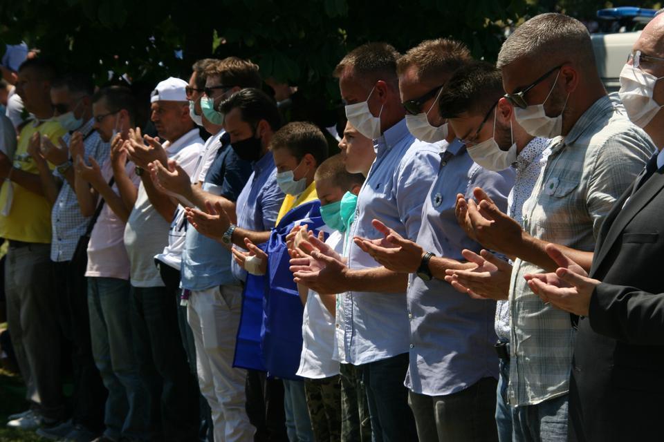 Bosna bayrağına bol dökümlü bir çocuk, 11 Temmuz 2020'de Temmuz 1995'te Srebrenica soykırımının dokuz yeni kurbanı için cenaze namazı kılan insanlar arasında.