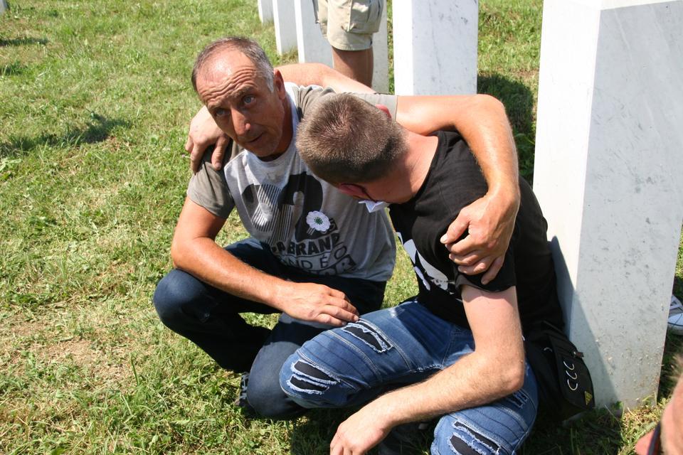 Bir adam, 11 Temmuz 2020'de 1995 yılında Srebrenica soykırımının dokuz yeni kurbanının gömülmesi sırasında arkadaşını teselli ediyor.