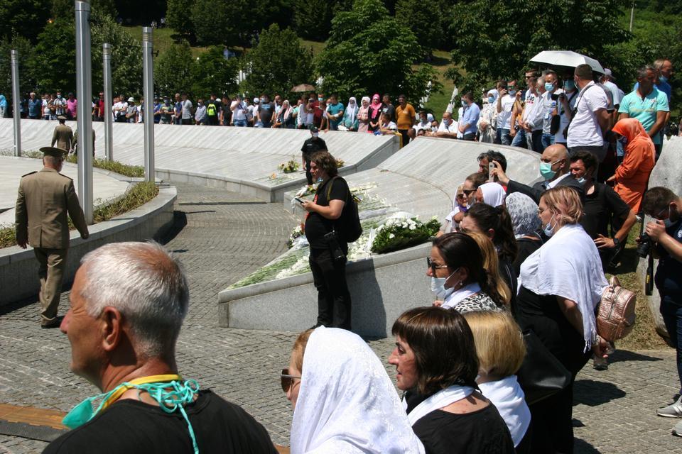 Kalabalıklar, Srebrenica soykırımı kurbanlarının adlarının bulunduğu bir anıtın etrafında duruyor. Katılımcılar bu yıl Srebrenica sakinleri ile ve 11 Temmuz 2020'deki Covid-19 kısıtlamaları nedeniyle ölenlerin ailesi ve arkadaşları ile sınırlıydı.