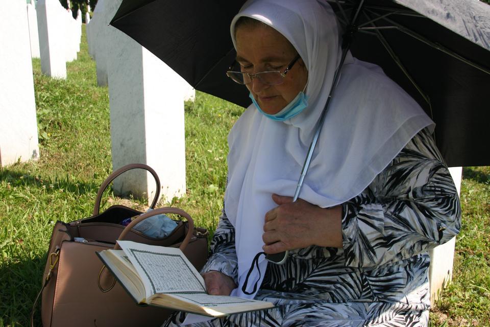 11 Temmuz 2020'de Srebrenica Soykırım Anıtı'ndaki mezarlar arasında otururken Kuran'dan bir kadın okuyor.