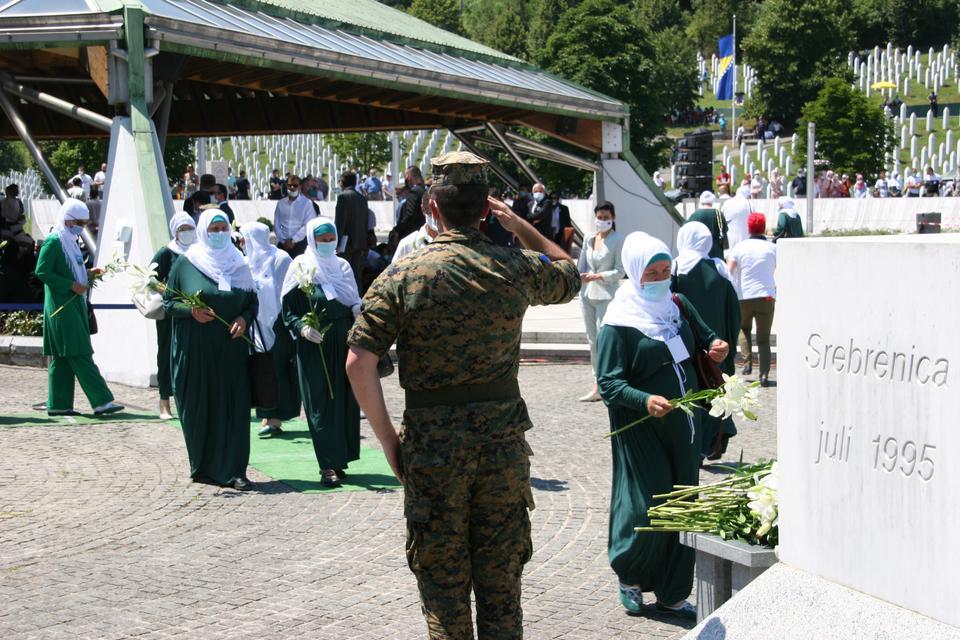 Yeşil giyinmiş Srebrenica grubunun anneleri Srebrenica anıtına çiçek yerleştirmek için sıraya giriyor. Her biri soykırım sırasında 11 Temmuz 2020'de iki hafta içinde 8 binden fazla Bosnalı erkek ve erkeği öldü.