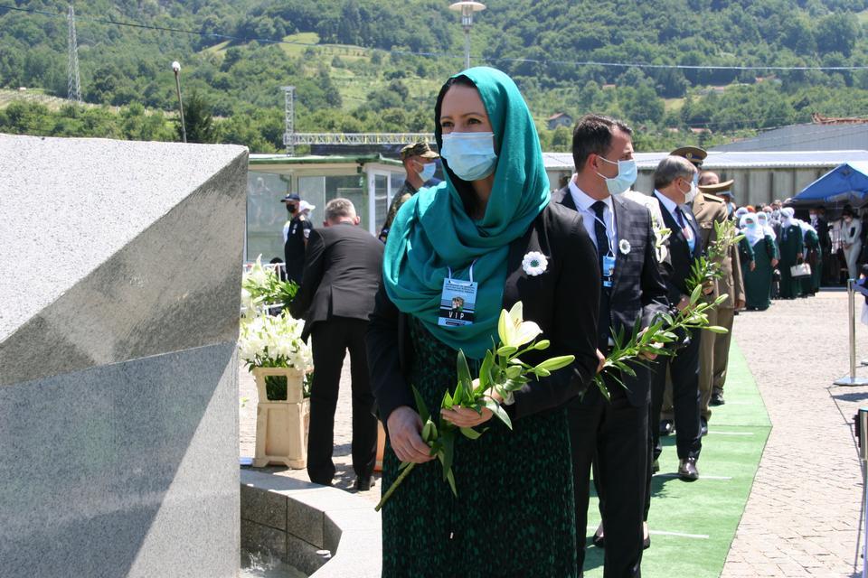 Srebrenica soykırım çiçeği giyen yas tutanlar ölüleri onurlandırmak için sıraya girer. 11 yaprak 11 Temmuz'u, beyaz ise masumiyeti temsil eder ve yeşil 11 Temmuz 2020'de umut anlamına gelir.