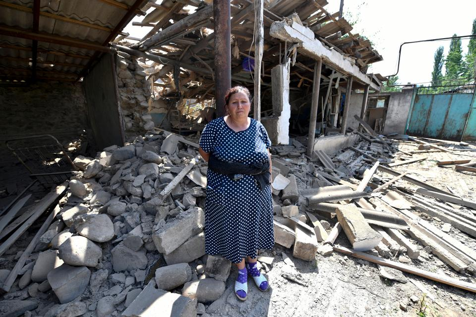 In this photo taken on Thursday, July 16, 2020, a woman stands in front of her damaged home after the shelling by Armenian forces in the Tovuz region of Azerbaijan.