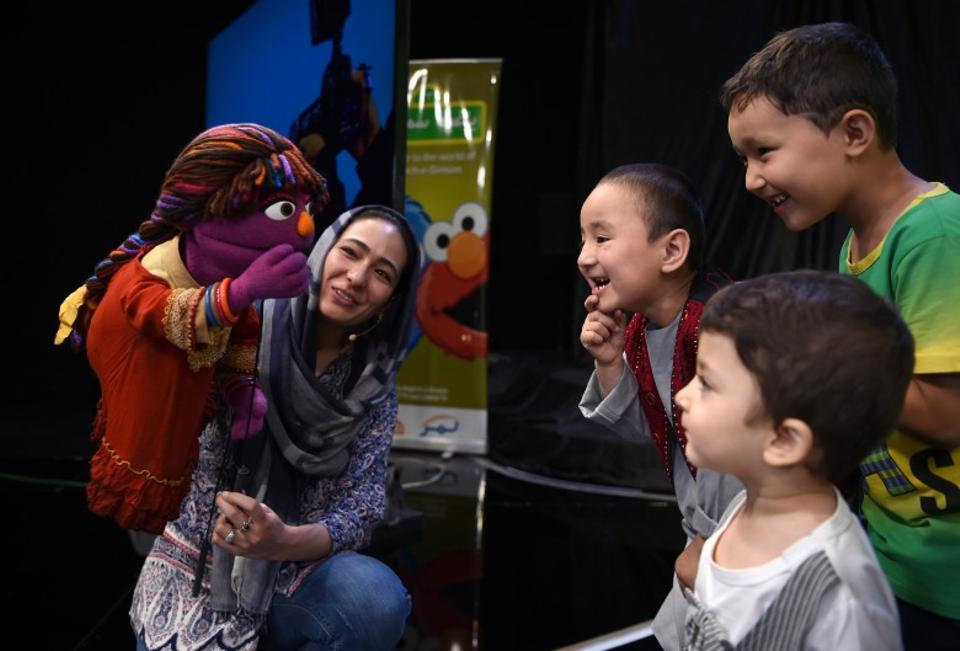 Afghan children meet a Sesame Street muppet called Zari after a recording at a television studio in Kabul on July 2, 2017