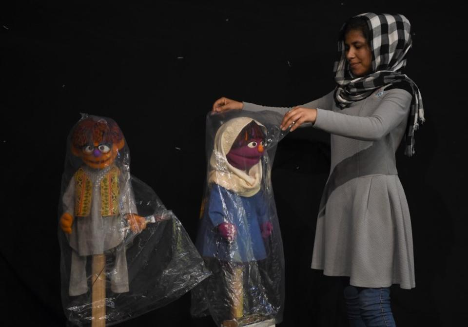 An Afghan puppeteer covers Sesame Street muppets Zari and Zeerak after a recording at a television studio in Kabul on July 2, 2017