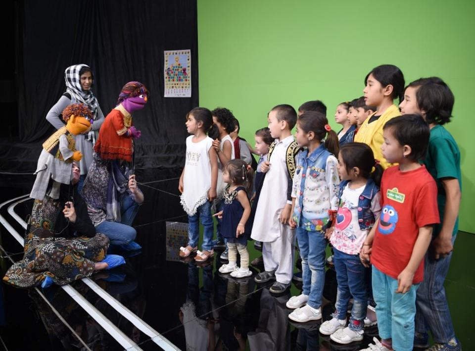 Afghan puppeteers hold Sesame Street muppets Zeerak and Zari as they meet children after a recording at a television studio in Kabul on July 2, 2017