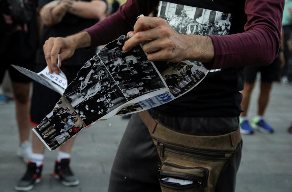 Bir protestocu, 9 Ağustos 2020'de İspanya'nın Madrid kentinde İspanya monarşisine karşı düzenlenen yürüyüş sırasında kraliyet ailesinin fotoğraflarını yok etti.
