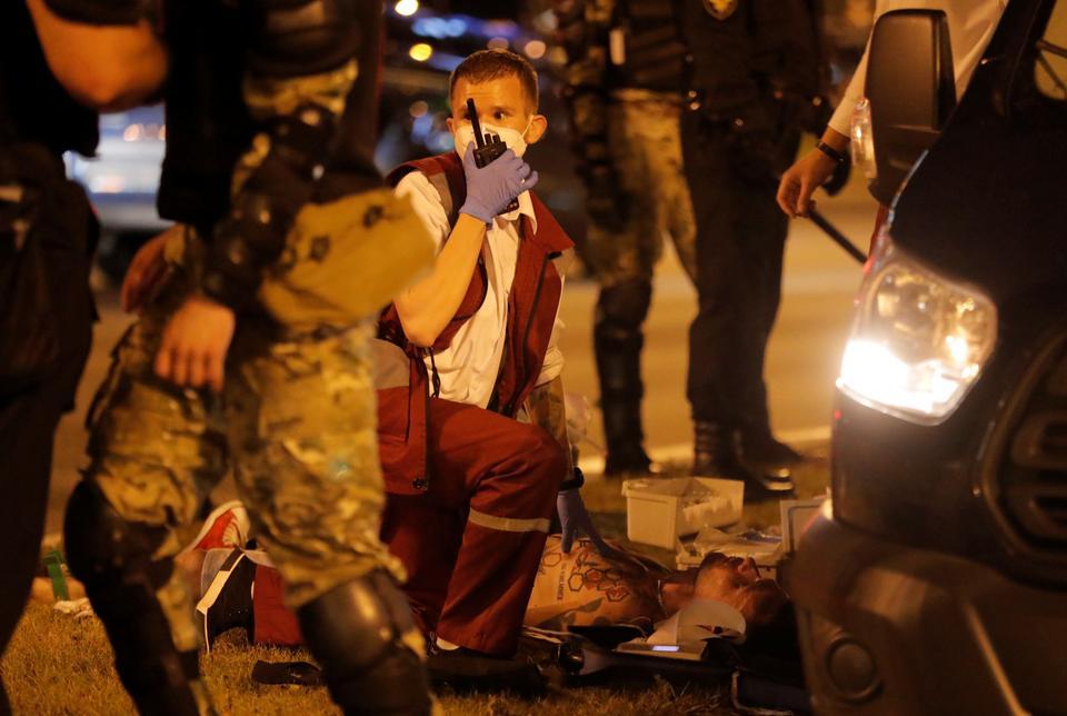Beyaz Rusya'nın Minsk kentinde 9 Ağustos 2020'de yapılan cumhurbaşkanlığı seçimlerinde sandıkların kapatılmasının ardından muhalefet destekçileriyle çatışmalar sırasında yerde yatan bir adam yardım alıyor.
