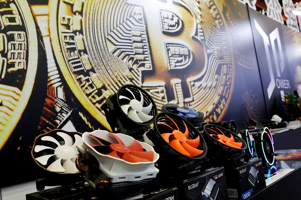 Cryptocurrency mining computer fans are seen in front of bitcoin logo during the annual Computex computer exhibition in Taipei, Taiwan June 5, 2018.