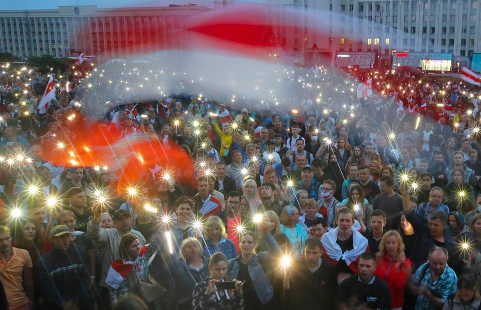 Belarus muhalefet destekçileri, Minsk, Belarus'taki Bağımsız Meydan'da hükümet binası önünde düzenlenen protesto mitingi sırasında telefon ışıklarını yakıyor ve eski Belarus ulusal bayraklarını dalgalandırıyor. 19 Ağustos 2020.