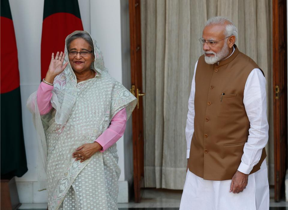 Indian Prime Minister Narendra Modi, right, watches his Bangladeshi counterpart Sheikh Hasina wave to the media before their meeting in New Delhi, India, Saturday, Oct. 5, 2019. Hasina arrived in India on Thursday for a visit during which she is expected to sign agreements on increasing trade and investment and improving regional connectivity.