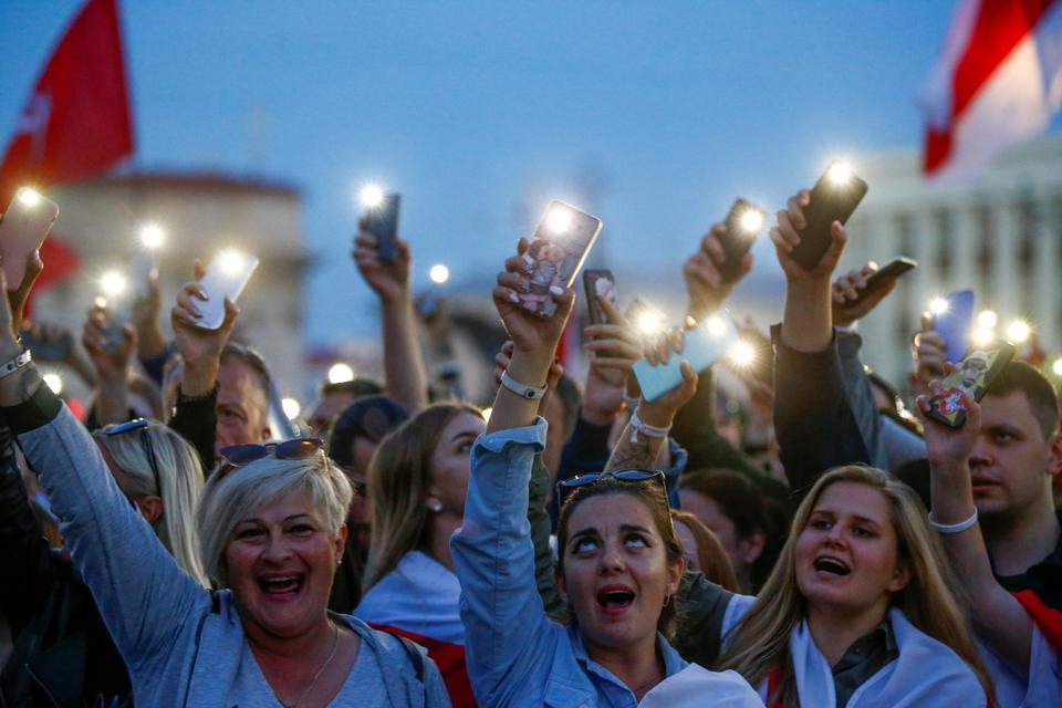 22 Ağustos 2020 Beyaz Rusya'nın Minsk kentindeki Bağımsızlık Meydanı'nda cumhurbaşkanlığı seçim sonuçlarına karşı yapılan muhalefet gösterisi sırasında insanlar telefonlarından ışık yakıyor.