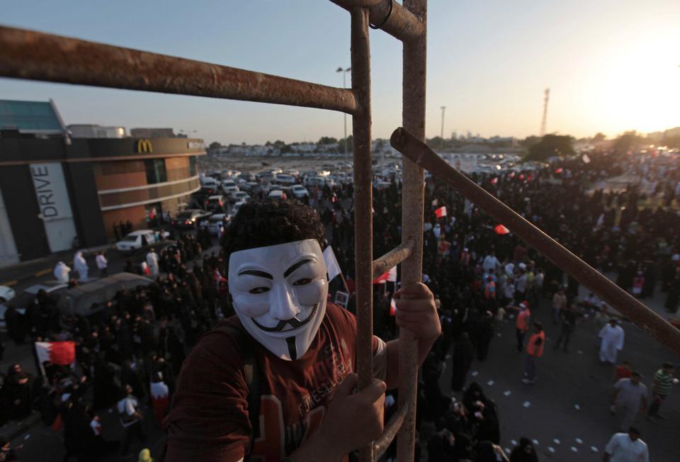 Dalam file foto 27 September 2013 ini, seorang pengunjuk rasa anti-pemerintah Bahrain yang mengenakan topeng memanjat perancah untuk memotret protes, di sebelah barat Manama, Bahrain.