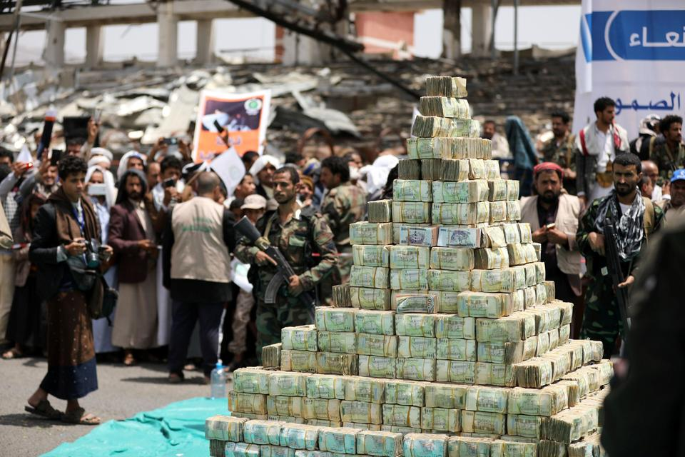 Houthi followers stand by bills of Yemeni currency during a ceremony held by Houthis to collect supplies for their fighters battling government forces in various frontlines, in Sanaa, Yemen September 24, 2020.