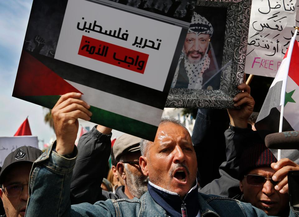 A Tunisian protester holds a placard that shows the Palestinian flag and Arabic that reads,