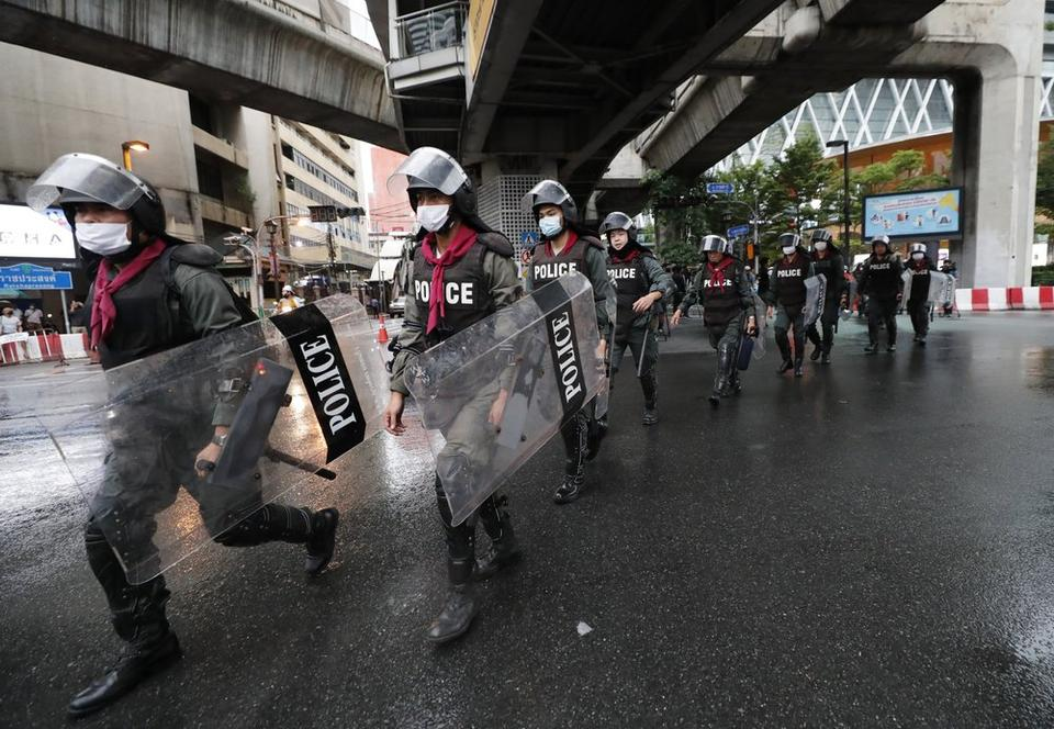 Thai police with riot shields take position in a business district where anti-government protesters said they will meet in Bangkok, Thailand, Friday, Oct. 16, 2020.