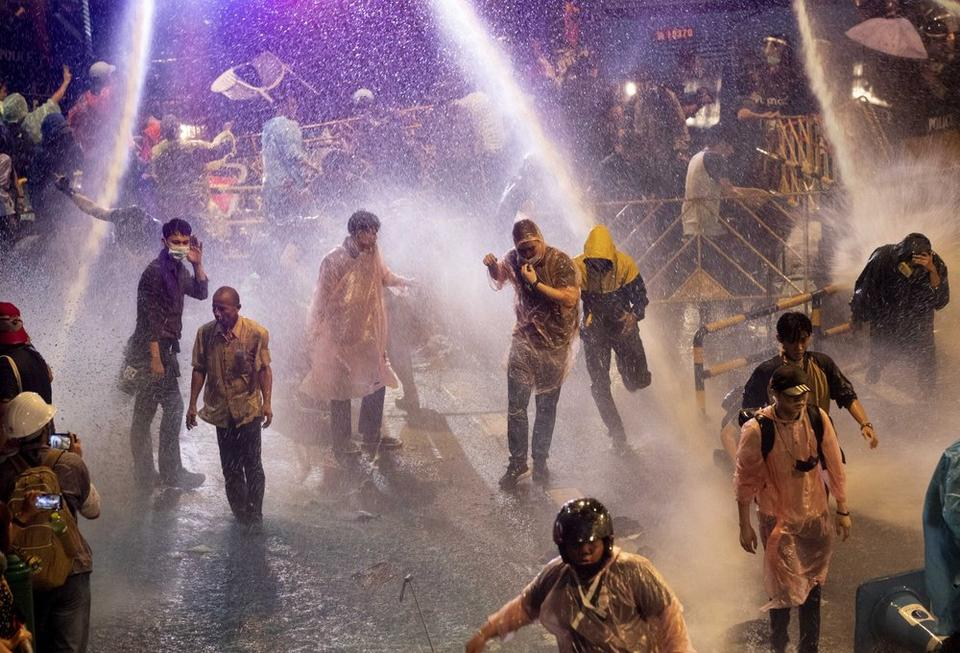 Pro democracy demonstrators face water canons as police try to disperse them from their protest venue in Bangkok, Thailand, Friday, Oct. 16, 2020.