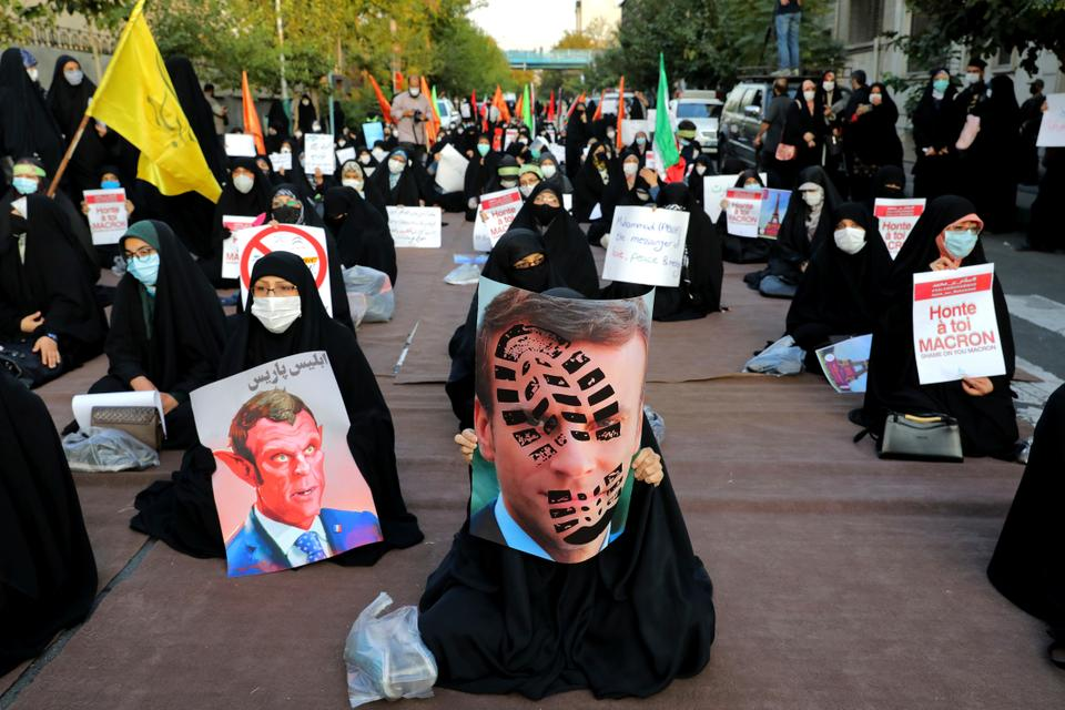 Iranian protesters hold defaced pictures of French President Emmanuel Macron during a protest against Macron in Tehran, Iran, on October 28, 2020.