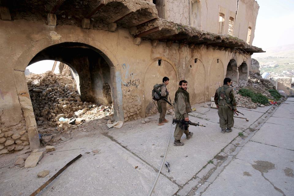 PKK terrorists are seen in the damaged streets of Sinjar, Iraq on Jan. 29, 2015.