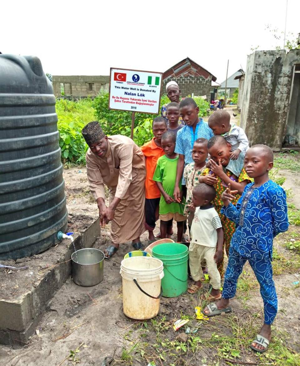 Local Nigerians are in front of water wells constructed by Turkish volunteers in 2018.