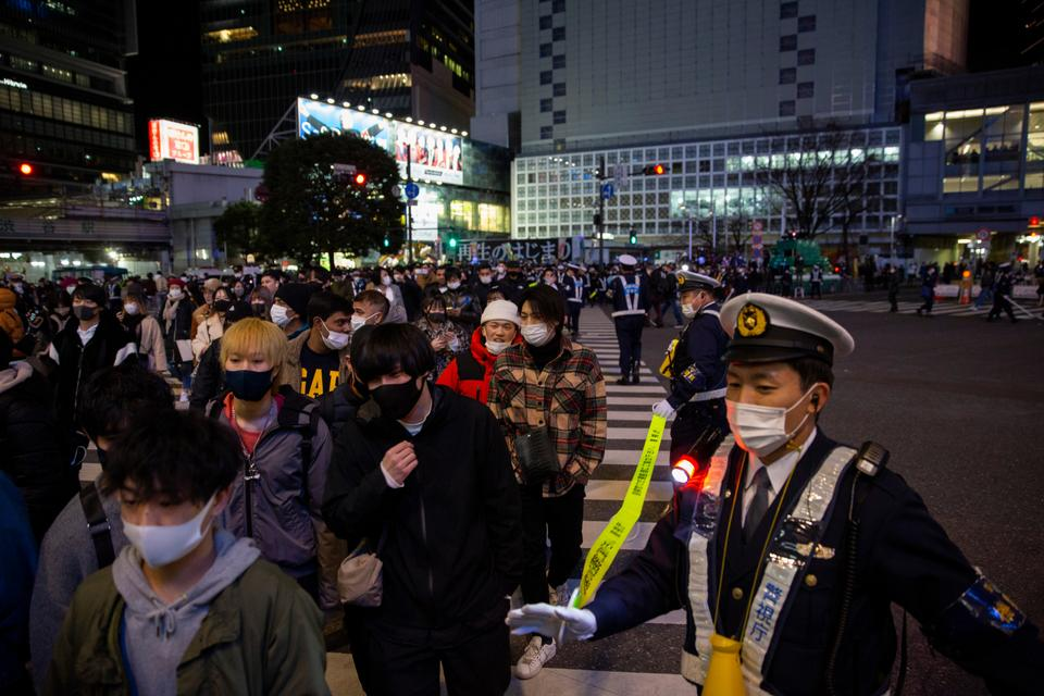 Police direct visitors around Shibuya crossing, a popular location for New Year's Eve gathering in Tokyo, January 1, 2021.