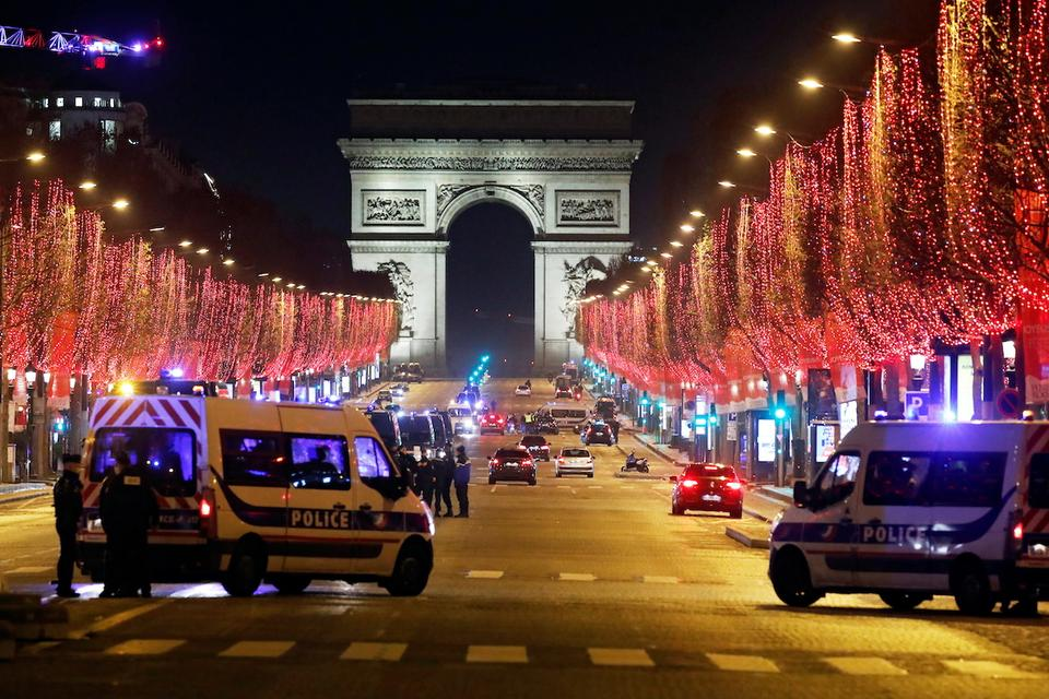 French police patrol on the Champs Elysees avenue in Paris after celebrations and gatherings have been banned due to Covid-19 restrictions in France, December 31, 2020.