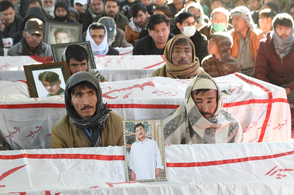 Mourners from the Shiite Hazara community gather next to the coffins of miners, who were killed in an attack by gunmen in the mountainous Machh area, during a sit-in protest at the eastern bypass on the outskirts of Quetta on January 7, 2021.