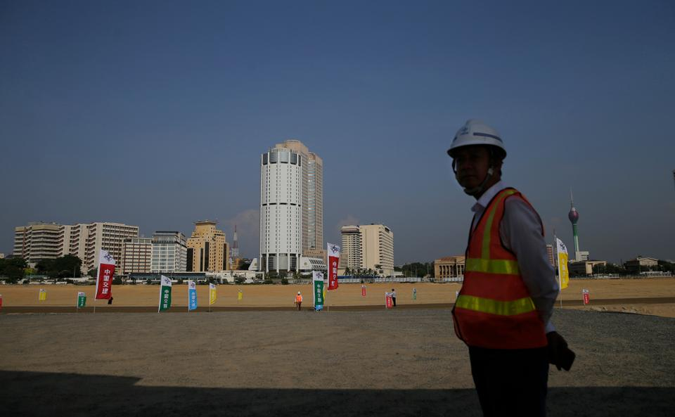 Chinese construction worker stands on land that was reclaimed from the Indian Ocean for the Colombo Port City project, initiated as part of China's ambitious Belt and Road Initiative.