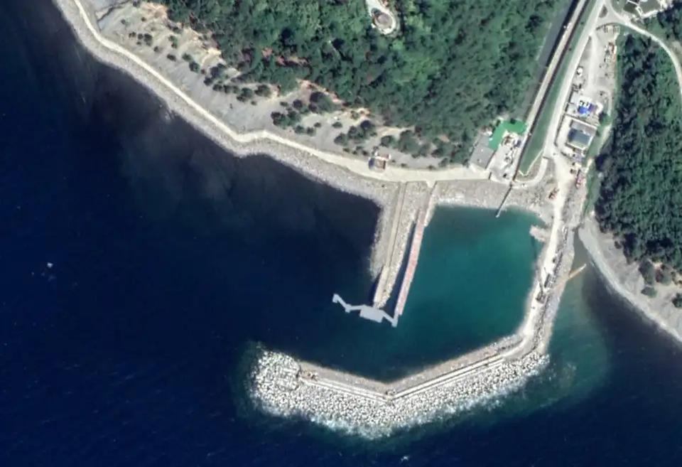 A satellite image of the enclosed harbor with the reported tunnel exit visible just above and to the left of the dock.