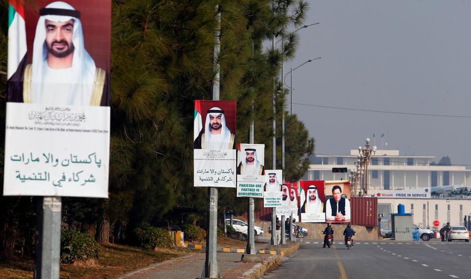 Motorcyclists ride past billboards showing the portraits of Abu Dhabi's Crown Prince, Sheikh Mohammed bin Zayed Al Nahyan, and Pakistani Prime Minister Imran Khan, in Islamabad, Pakistan, Sunday, Jan. 6, 2019.