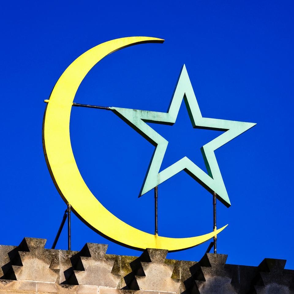 Muslim crescent moon and star over main door of Paris Great Mosque, France.