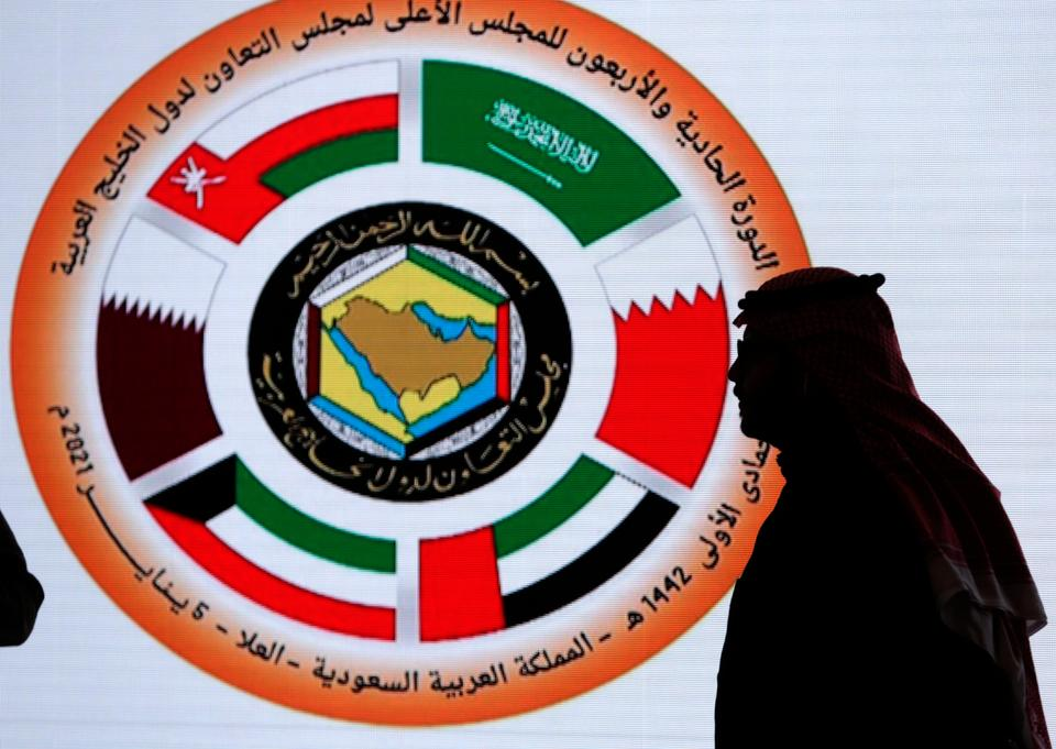 A Saudi television anchor stands in front of the logo of the 41st Gulf Cooperation Council (GCC) at the media center in at Al Ula, Saudi Arabia, Tuesday, Jan. 5, 2021.