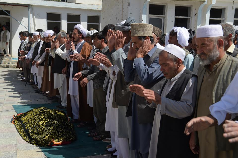 A security guard keeps watch as Afghan mourners and relatives pray in front of the coffin of one of the victims of a suicide attack, on a Shia mosque a day earlier, in Kabul on August 26, 2017.