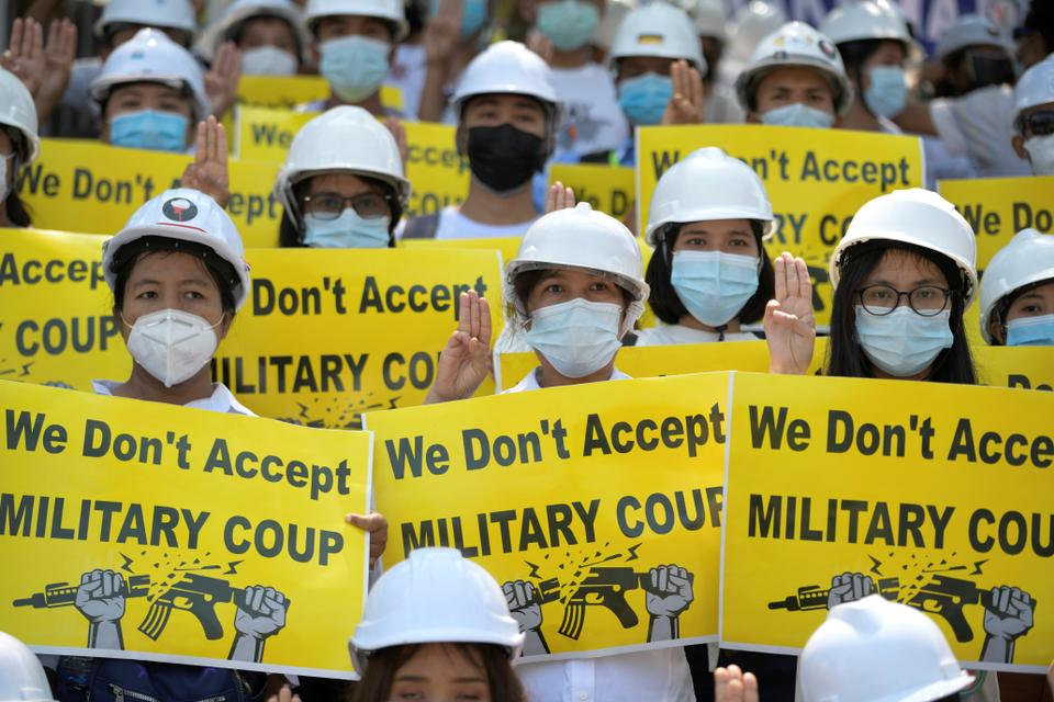 Demonstrators hold placards as they rally against the military coup in Yangon, Myanmar, February 24, 2021.
